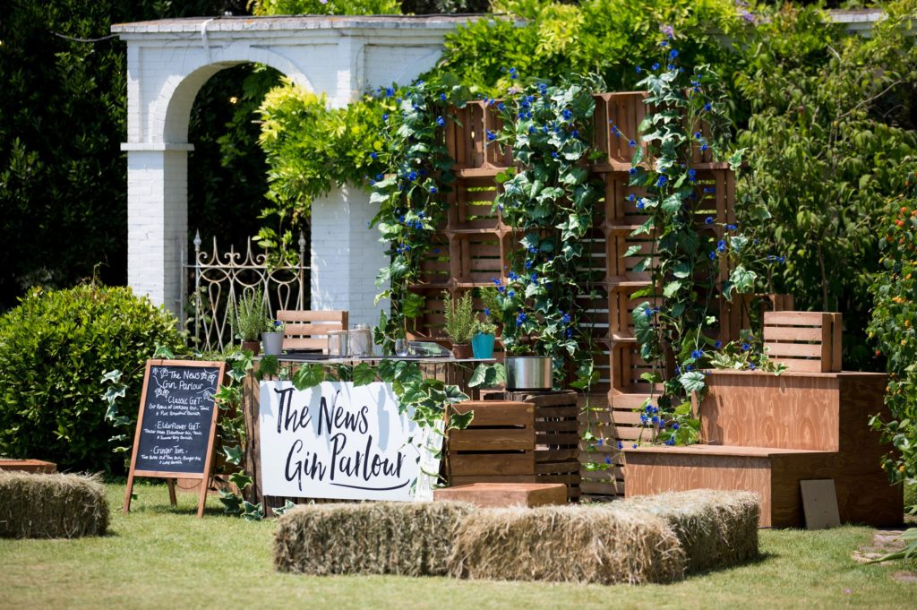 Custom build branded experience gin parlour with rustic hay-bale seating and greenery