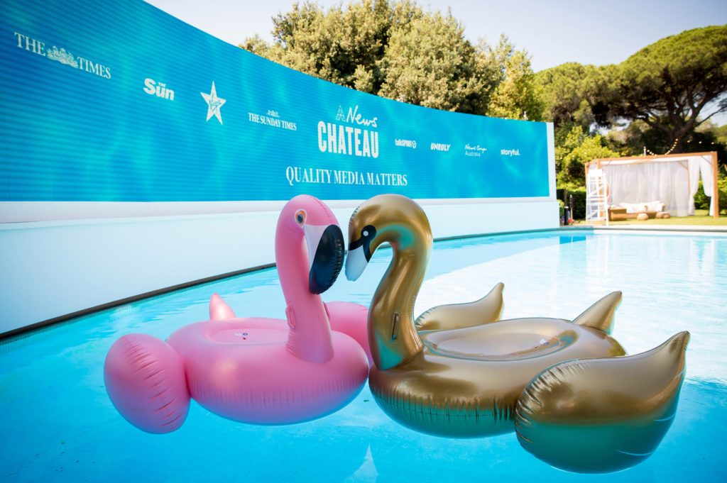 News Chateau curved LCD screen showing brand logos, positioned around pool with inflated flamingo swimming toys as props