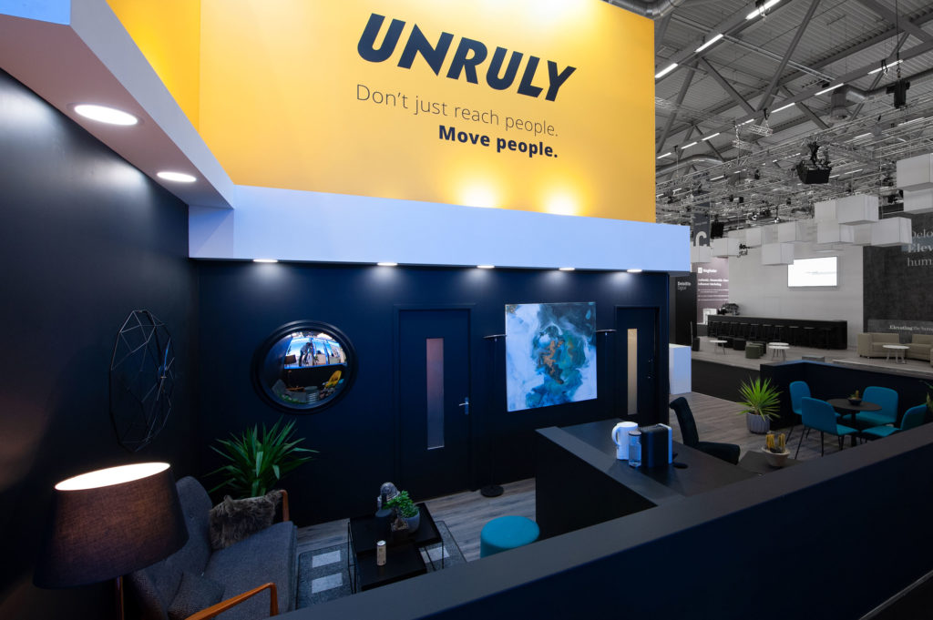 Unruly exhibition stand, sideview, showing meeting pods and custom branding