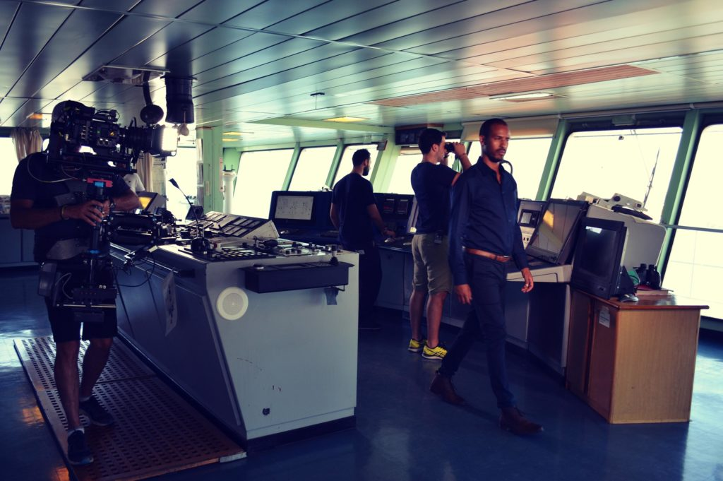 film crew and actor in naval ship bridge, shooting Inmarsat 40th Anniversary communications film