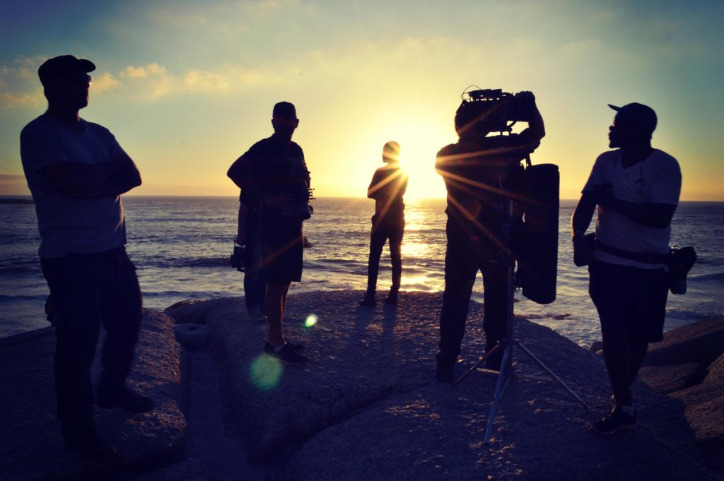 Silhouetted film crew in front of ocean, onsite making Inmarsat 40th Anniversary communications film