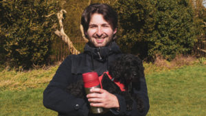 Digital Designer holding coffee thermos and dog in park